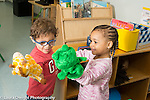 Preschool 2-3 year olds boy and girl using puppets to talk and play
