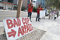 "Phoenix, Arizona. July 24, 2012 - A sign reading ""Bad Cop Arpaio,"" in reference to Maricopa County Sheriff Joe Arpaio's law enforcement policies on illegal immigration, lies next to protesters Raul Cordero (left) and Sergio Juarez (center), who demonstrate against the sheriff. Maricopa County Sheriff Joe Arpaio testified in court on July 24, 2012 to respond to accusations his office (MCSO) has been racial profiling Latinos as they enforce local immigration laws in the county. The lawsuit is known as Ortega-Melendres vs. Arpaio. Photo by Eduardo Barraza © 2012"