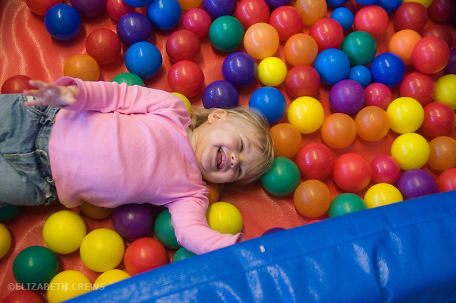 Berkeley CA Girl, one and a half, deliriously happy in ball bin at a Children's Creative Play Space  MR