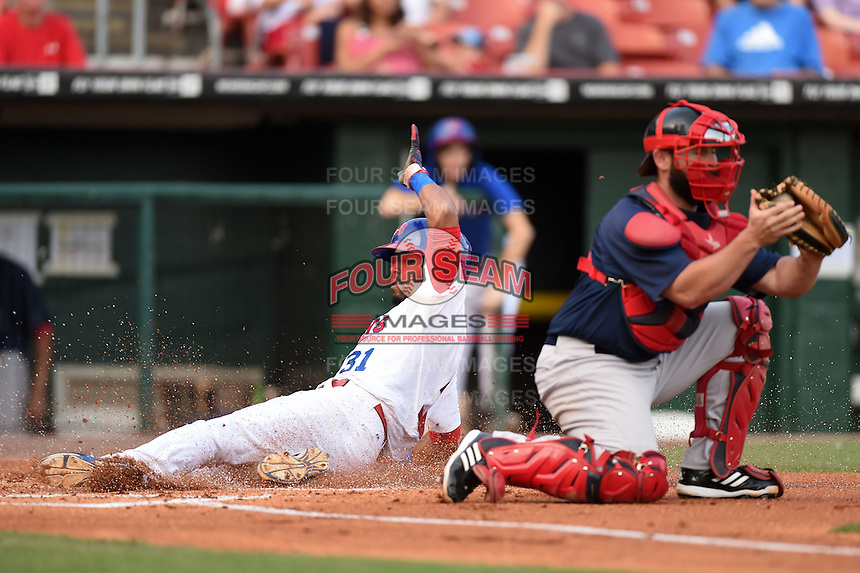 Buffalo Bisons outfielder Dalton Pompey (31) slides safely into home behind catcher Dan Butler (12) during a game against the Pawtucket Red Sox on August 26, 2014 at Coca-Cola Field in Buffalo, New  York.  Pawtucket defeated Buffalo 9-3.  (Mike Janes/Four Seam Images)
