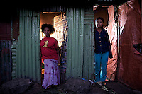 """Weinit, 24, on left and Busunesh, 27, on right, escaped from the same village in Ethiopia a decade before after being sold into marriage by their families, only to fall into commercial sex work in the """"Merkato"""" neighborhood of Addis Ababa, Ethiopia's capital on February 20, 2009...While in decline, early child marriage is still widely spread in rural areas of Ethiopia where families sell their daughters into marriage at ages as young as 5 years old...Names of subjects have been fictionalized and specific locations have been omitted to protect the identities of the children portrayed in the story."""