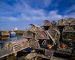 Lunenburg County, Nova Scotia<br /> Lobster traps stacked on the dock at Blue Rocks village, with a blue fishing boat and cabin in the distance