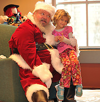 NWA Media/Michael Woods --12/20/2014-- w @NWAMICHAELW...Sadie Buonaiuto-Cloyed, age 5 from Fayetteville visits with Santa Saturday afternoon during the Christmas celebration at the Fayetteville Public Library.  The event gave children a chance to hear Santa Clause read Christmas stories, talk to Santa and have cookies and apple cider with their parents and santas helpers.