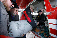 Saturday February 20, 2010.   Volunteers help load Iditarod airforce pilot Wes Erb's plane with a 100 lb. propane tank for delivery to the Rainy Pass checkpoint at Willow Airport.