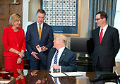 United States President Donald J. Trump hands the pen he used to sign the second of three Executive Orders concerning financial services to US Senator David Perdue (Republican of Georgia) at the Department of the Treasury in Washington, DC on April 21, 2017.  From left to right: US Representative Claudia Tenney (Republican of New York) Senator Perdue, the President, and US Secretary of the Treasury Steven Mnuchin.<br /> Credit: Ron Sachs / Pool via CNP
