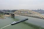 Foto: VidiPhoto<br /> <br /> NIJMEGEN - De Waalbrug in Nijmegen zit vol met kankerverwekkende chroom-6 verf. Daarom zijn volgens Rijkswaterstaat de onderhoudswerkzaamheden aan de brug nog niet begonnen. Dat is donderdag bekend geworden. Eerst moet de verflaag van de gehele brug verwijderd worden en dat is een specialistisch en tijdrovend proces. Er gelden strenge veiligheidsmaatregelen voor, vergelijkbaar met het verwijderen van asbest. De werkers die de verf eraf halen moeten beschermende pakken aan. Tevens moet de Waalbrug moet tijdelijk ingepakt worden. De Waalbrug moet ingrijpend gerenoveerd worden. De werkzaamheden zouden eigenlijk in juli dit jaar, vlak na de Vierdaagse, beginnen. Bouwbedrijf KWS werd echter volledig verrast door de aanwezigheid van de chroom-6 verf. Daar was bij de aanbesteding geen rekening mee gehouden. De verflaag is in 1992 aangebracht. Twee jaar later werd chroom-6 verboden, omdat de stof kankerverwekkend bleek. De stof wordt pas gevaarlijk als de verflaag wordt weggeschuurd, verhit of gestraald. De renovatie van de brug zou 36,5 miljoen gaan kosten. Hoeveel hoger dat bedrag gaat uitpakken, is nog niet bekend.