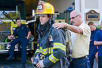 J.T Boyle is helped with his gear by Chief Glenn Hackbart at Eddington Fire Company Wednesday August 5, 2015 in Bensalem, Pennsylvania. (Photo by William Thomas Cain)