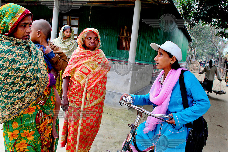 Info Lady Jeyasmin talks to a group of women during her rounds of rural villages. In rural Bangladesh the Info Ladies are bringing internet services to men and women who need information but don't have the means to access the web. After three months of training the Info Ladies set out each day in their pink and blue uniforms to cycle to remote villages where they provide Skype connections to villagers who want to communicate with relatives working overseas. They also provide tech services, photographs, health tests, cosmetics and other small items that can be easily carried.