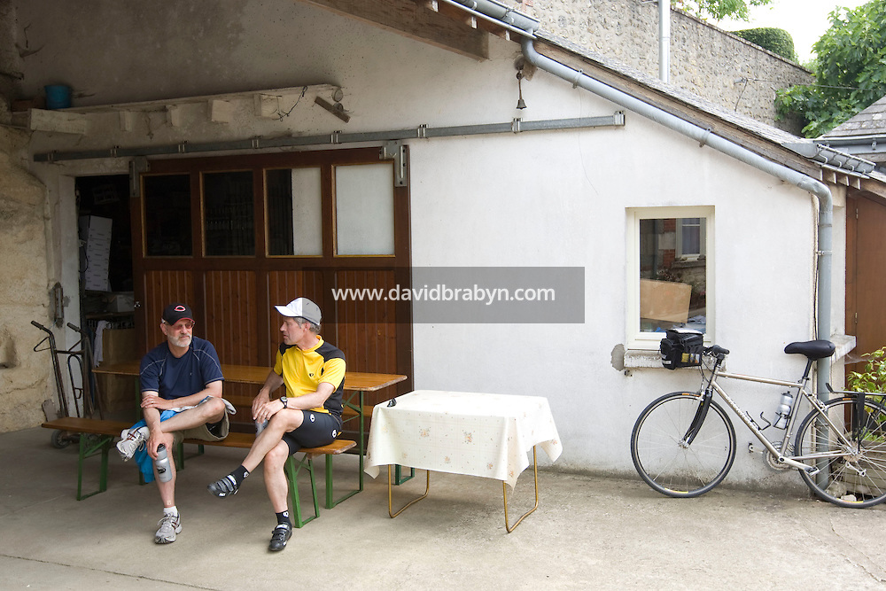 Larry Athan (R) and Larry Brodsky, participants in a Backroads cycle tour of the Loire Valley, talk after lunch outside winemaker Daniel Jarry's cellars in Vouvray, France, 26 June 2008.