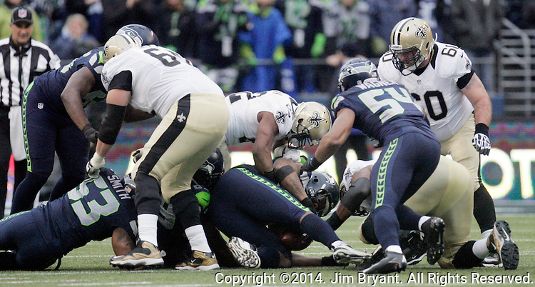 New Orleans Saints running back Mark Ingram (22) fumbles after being hit by  Seattle Seahawks Clinton McDaniel (69) during the 2nd round in a NFL Western Division playoff game at CenturyLink Field in Seattle, Washington on January 11, 2014.  Seahawks beat the Saints 22-15 to take home-field advantage in the NFL Championship Game. ©2014. Jim Bryant Photo. ALL RIGHTS RESERVED.