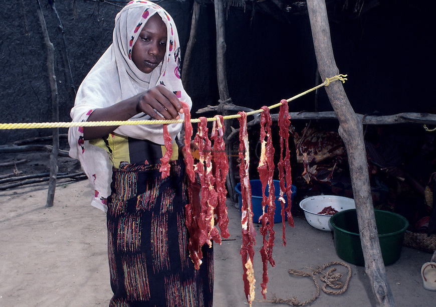 Young girl drying meat for preservation