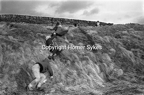 Children playing rolling down a bank  Yorkshire UK<br /> <br /> My ref 1a/117/1968
