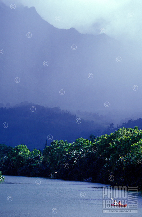 Couple paddling kayak on the Hanalei River with rainy Mount Waialeale in background, Kauai, Hawaii