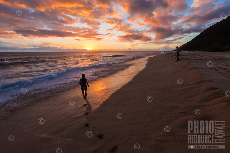 Beachgoers enjoy the beautiful sunset at the beach at Yokohama Bay, West O'ahu.