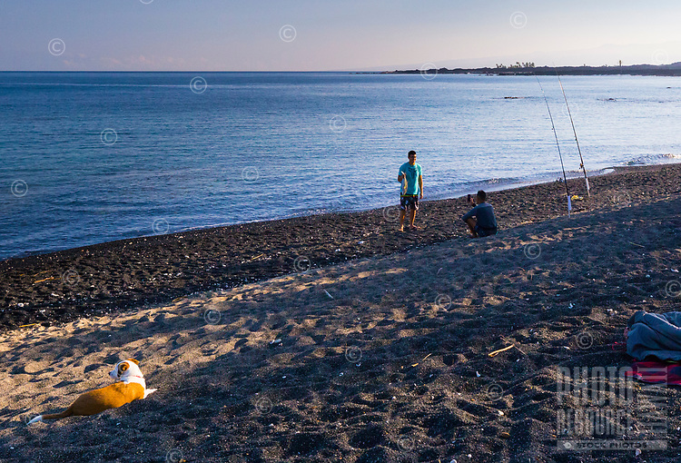 A man holds up the catch of the day during a beach camping trip along the western coast of Hawai'i Island.