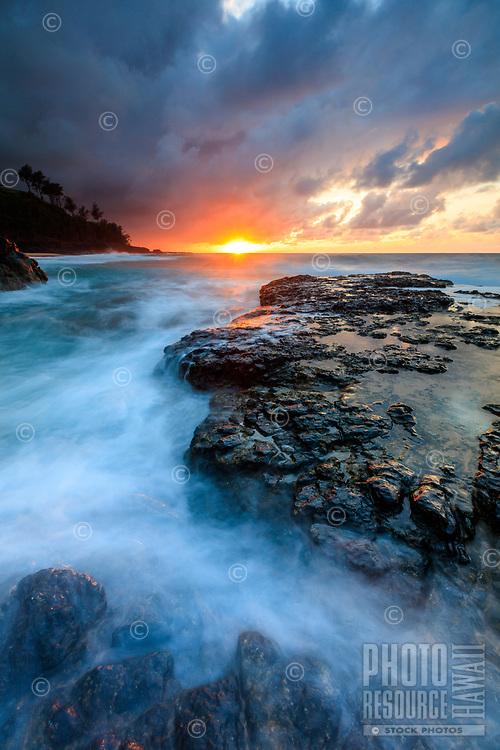 The ocean surf washes around a large lava rock at sunset at Secrets Beach, Kilauea, Kauai, Hawaii.