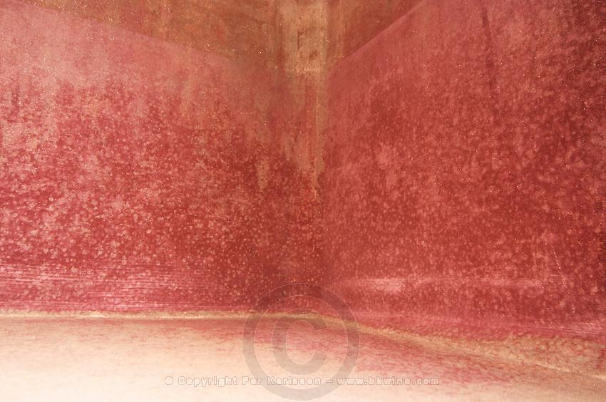 Inside a concrete fermentation vat, red crystal deposits. Domaine Gauby, Calces, roussillon, France