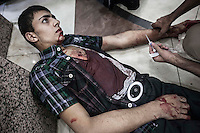 A Syrian civilian lies on the floor of a hospital as he gets medical assistance after was wounded by aircraft shelling over a bakery while was buying bread in a residential neighborhood in Aleppo. During last days the Assad's aircraft have targeted bakeries and residential neighborhood killing daily dozens of civilians in Aleppo City.