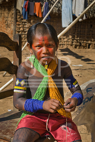 Pará State, Brazil. Aldeia Pukararankre (Kayapo). Boy with bead decorations and body and face paint; shaved top of head.