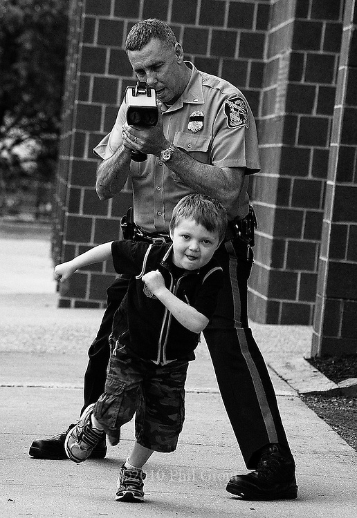Photo by Phil Grout..Six-year old Grant Bierce of Columbia really isn't running from the law.   Lt. Paul Yodzis of the Howard County Police Department is in the process of clocking the young speedster as he races up the sidewalk in front of Guildford Elementary School in Oakland Mills.  It's all part of a wellness fair the school hosted Friday. and for Grant, he's doing pretty well at 10 m.p.h.