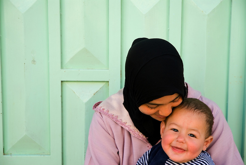 A young Moroccan woman and baby share a smile in the pale turquoise city of Sefrou.