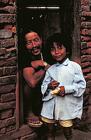 Father wearing sandals sits in doorway with arms folded on knees; young son stands; both full face; son 3 4 length. Kathmandu, Nepal.