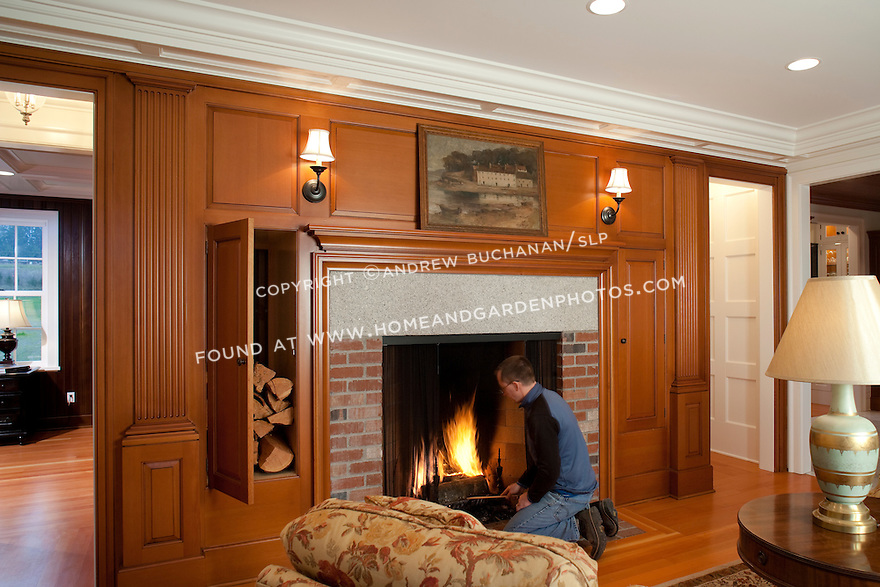 In the fireplace room of this new contemporary home built in a clean, traditional Shaker style, cherry paneling surrounds the masonry fireplace capped with an 800 pound granite lintel.  On the wall opposite the fireplace, French doors and traditional six over six double hung windows flood the room with natural light, even on gray Northwest winter afternoons.  The homeowner, shown here tending the fire, is a cabinetmaker with a Master's degree in art who designed the house and crafted all of the cabinetry, built-ins, and most other woodwork himself.