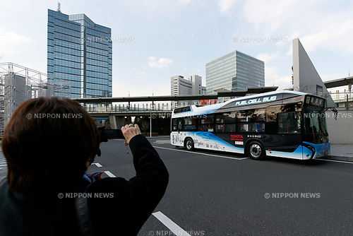 A woman takes pictures of a hydrogen fuel cell bus at Tokyo Big Sight on March 23, 2017, Tokyo, Japan. From March 21, the Tokyo Metropolitan Government Bureau of Transportation has been operating two hydrogen fuel cell buses on the route between Tokyo Station and the International Exhibition Center (Tokyo Big Sight). The new public transports, developed by Toyota Motor Corporation, are part of the bureau plan to contribute to a ''hydrogen society''. (Photo by Rodrigo Reyes Marin/AFLO)
