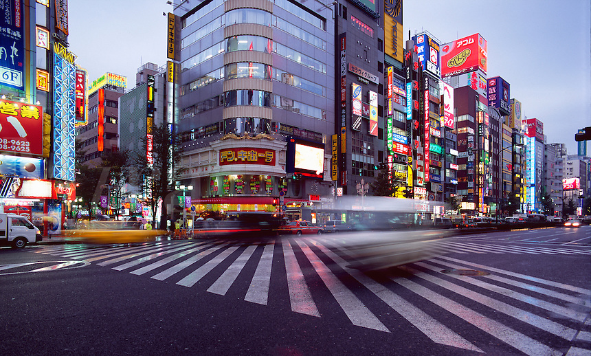 Neon-lit buildings and passing traffic in Shinjuku entertainment area, Tokyo; evenin