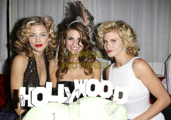 ANNALYNNE McCORD, RACHEL McCORD & ANGEL McCORD.Rachel McCord's 21st Birthday Party held at the Mondrian Hotel's Sky Bar, West Hollywood, California, USA. .October 27th, 2009 .half length orange yellow tulle dress silver feather in hair beige red lipstick white sleeveless dress brown black beads beaded sequins sequined plunging neckline cleavage red sisters family halterneck cake food dessert .CAP/ADM/KB.©Kevan Brooks/AdMedia/Capital Pictures.