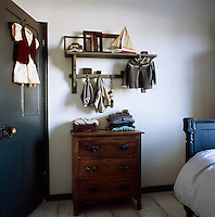 A detail of a child's bedroom in white and grey. A selection of knitwear hangs from hooks and is folded neatly on top of a wooden chest of drawers.