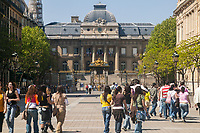 Students and tourists walk near the Palais de Justice on the Ile de la Cite in Paris, France.