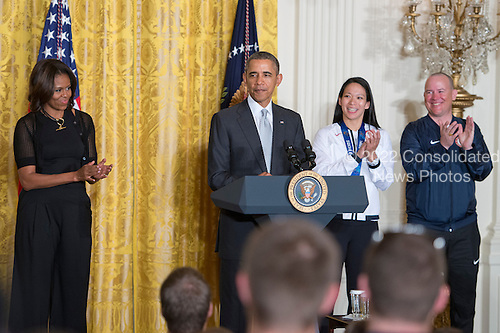 United States President Barack Obama and First Lady Michelle Obama welcome members of the United States teams and delegations from the 2014 Olympic and Paralympic Winter Games in Sochi to the White House in Washington, D.C. on Thursday, April 3, 2014.  From left to right: Michelle Obama, President Obama, Julie Chu of Fairfield, Connecticut, Women's Ice Hockey and 2014 Winter Olympic Games Closing Ceremony Team USA Flag Bearer, and Jon Lujan of Littleton, Colorado, Paralympics Alpine Skiing, a former United States Marine Corps Sergeant and 2014 Winter Paralympic Games Opening Ceremony Team USA Flag Bearer.<br /> Credit: Ron Sachs / Pool via CNP