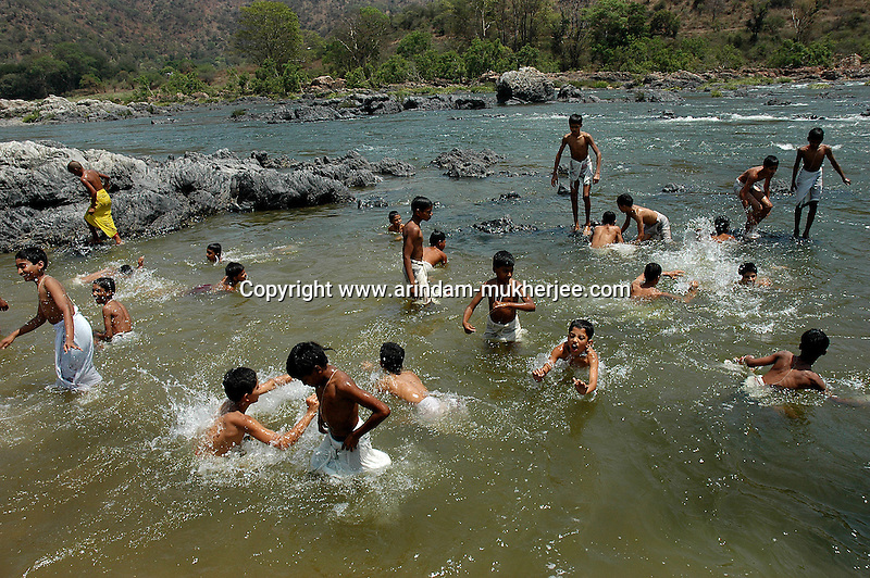Students of Om Shantidhama swimming in the river Cauvery. Om Shantidhama is a residential vedic school for boys. Nestled among the confluence of hills, forest and rivers - Om Shanti Dhama is a world removed from the maddeningly fast and often chaotic urban India. Students from allover the country are selected to take part in its Vedic and free education system. What is unique about this institute is that they have blended the traditional and modern education system. Here computer and science is taught with the same passion as the Vedas and Shastras, helping the students to grow spiritually as well as earn a living. Bonding with the nature and animal world is a mandatory part of the institute's curriculum. Karnataka, India. Arindam Mukherjee