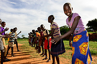 UGANDA, Karamoja, Loyoro Parish, Karamojong tribe, children dancing at church compound / Karamojong Ethnie, Kinder fuehren tadtionelle Taenze auf