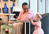 NWA Democrat-Gazette/CHARLIE KAIJO Olga Hamilton of Rogers greets Safia Sadikova, 1, of Fayetteville as she makes art during a drop-in art making class, Sunday, July 7, 2019 at Crystal Bridges Museum in Bentonville. <br /> <br /> Guest artist, Michael Albert, showed guests how to make art using upcycled cardboard from discarded consumer packaging. The New York native is on a multi-state tour.