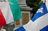 """A Quebec and a """"patriot"""" flag fly in front of Wolfe's monument on the Plains of Abraham in Quebec city July 1, 2009. The RRQ held their annual protest against Canada by collecting Canada flags to """"send them back to the sender""""."""
