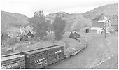 A wide-angle view of leased D&amp;RGW #464 departing Durango with a freight train on the east approach curve to Animas River Bridge 451-A.  The Graden Flour Mill is in the background.<br /> RGS  Durango, CO  Taken by Richardson, Robert W. - 10/3/1951