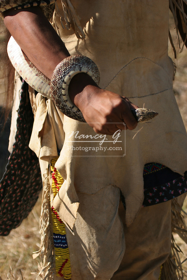 A Native American Indian boy holding the head of a snake that he caught in a tipi Indian village