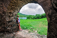 Youn woman looking through arch at Peace Hill. St. John. Virgin Islands National Park.