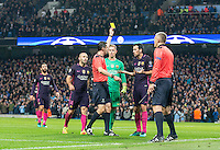 Sergio Busquets of Barcelona is shown a yellow card from Referee Viktor Kassai (Hun) as Man City celebrate there 3rd goal during the UEFA Champions League match between Manchester City and Barcelona at the Etihad Stadium, Manchester, England on 1 November 2016. Photo by Andy Rowland / PRiME Media Images.