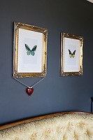 In the living room butterfly prints are displayed in vintage gilded frames and are set against walls painted a stunning dark graphite