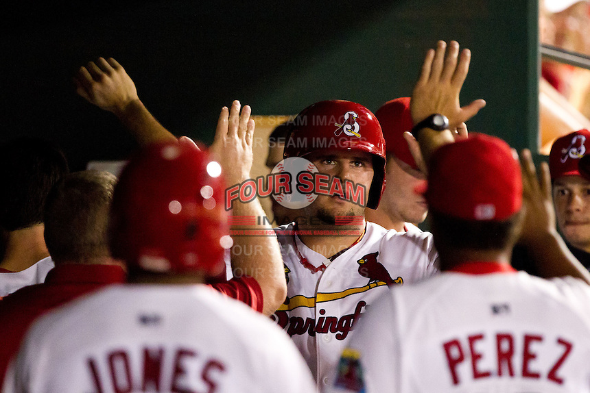 Matt Adams (25) of the Springfield Cardinals is congratulated by teammates in the dugout after scoring during a game against the Northwest Arkansas Naturals at Hammons Field on August 1, 2011 in Springfield, Missouri. Springfield defeated Northwest Arkansas 7-1. (David Welker / Four Seam Images)