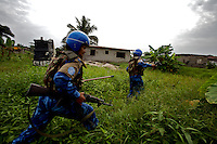 Indian female Peacekeepers from the Indian FPU ( formed police unit ) chase running liberian men during a cordon and search operation in the  in Monrovia, Liberia on Monday March 19 2007. .103 Indian police personnel  were specially selected to take part in the UNMIL peacekeeping mission in Liberia for an initial deployment of 6 months. .They are the first contingent entirely formed by women in the history of the United Nations Peacekeeping..their mission in the country is to provide fire support to the unarmed liberian security forces. In india these women distinguished themselves by operating in the most troubled areas of the country taking part in counter insurgency and crowd control special operations.