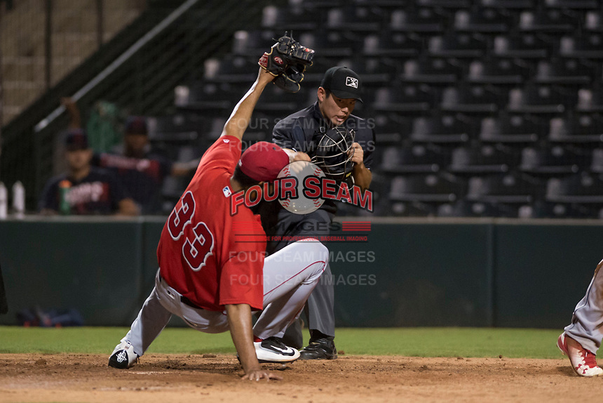 Home plate umpire Shin Koishizawa calls Felix Fernandez (not pictured) out after being tagged by AZL Angels relief pitcher Cristia Reyes (33) during an Arizona League game against the AZL Indians 2 at Tempe Diablo Stadium on June 30, 2018 in Tempe, Arizona. The AZL Indians 2 defeated the AZL Angels by a score of 13-8. (Zachary Lucy/Four Seam Images)