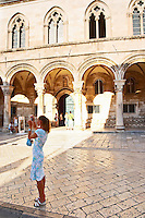 A young slender woman in short white dress taking a photograph in front of arched porch of the Rector's Palace Knezev Dvor on the Pred Dvorom street Dubrovnik, old city. Dalmatian Coast, Croatia, Europe.