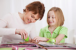 USA, Illinois, Metamora, Mother and daughter (8-9) making arts and crafts at table