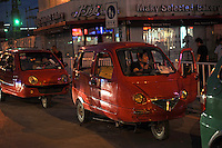 Local made three wheel taxi cars wait at a shopping center in Shenyang..