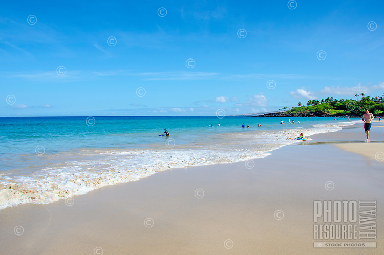 Man jogging and children playing at Hapuna Beach, along the Big Island's Kohala Coast. This white sand beach has been rated one of the best beaches in the world time and time again.