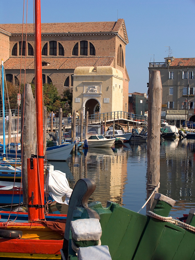 Fishing boats and houses along the Vena canal with city gate and Duomo Chiesa Catterdrale in back, Chioggia Ital